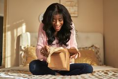 Happy african american woman unboxing package in bedroom stock images