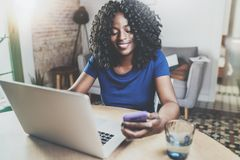 Happy african american woman using laptop and smartphone while sitting at wooden table in the living room.Horizontal Royalty Free Stock Image