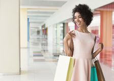 Happy african-american woman walking in shopping center. Happy african-american woman walking with coloured shopping bags in shopping center Royalty Free Stock Photos