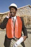 Happy African American worker. With blueprints using cell phone at construction site royalty free stock images