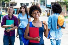 Happy african american young adult woman with students in city. Happy african american young adult women with students in city in summer royalty free stock photo