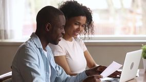 Happy african american young couple paying bills online at home