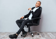 Happy african american young man sitting in leather office chair Royalty Free Stock Photo