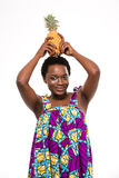 Happy african american young woman holding pineapple on her head stock photos