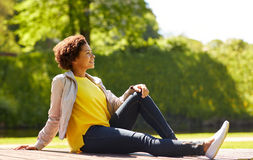 Happy african american young woman in summer park Stock Photo
