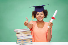 Happy african bachelor girl with books and diploma Stock Photos