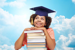 Happy african bachelor girl with books over sky Stock Photo