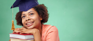 Happy african bachelor girl with books at school Stock Image