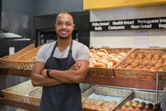 Happy african baker man. Smiling baker man standing with fresh bread at bakery. Happy african man standing with crossed arms at counter in bake shop and looking royalty free stock photos