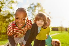 Happy african boy and his friends. In multicultural kindergarten stock images