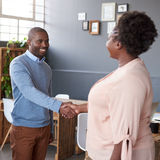 Happy African business partners shaking hands together in an office. Young African businesspeople dressed casually standing in a large grey modern office smiling stock image