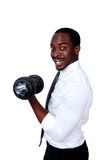 Happy african businessman lifting dumbbells. Portrait of a happy african businessman lifting dumbbells on white background Royalty Free Stock Images