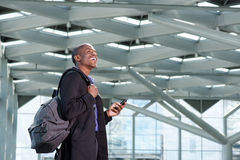 Happy african businessman with mobile phone and bag. Side portrait of happy african businessman walking with mobile phone and bag Stock Photography