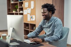 Happy african businessman using computer royalty free stock image