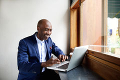 Happy african businessman working on laptop at cafe Royalty Free Stock Photos