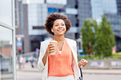 Happy african businesswoman with coffee in city Royalty Free Stock Images