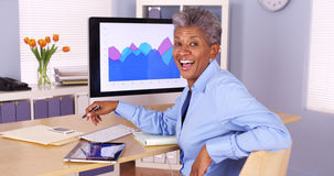 Happy african businesswoman sitting at desk Royalty Free Stock Photography