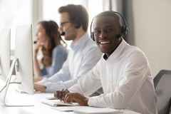Happy african call center agent in headset posing at workplace