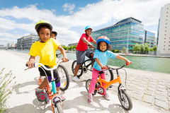 Happy African children cycling along the river. Group of happy age-diverse African children cycling together along the river at sunny day Stock Image