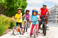Happy African children in helmets riding bikes. Four happy age-diverse African children in safety helmets riding bikes on cycle lane in summer Royalty Free Stock Images