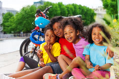 Happy African children resting after cycling. Happy African boys and girls resting after cycling, sitting together on bicycle path in summer Stock Image