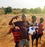 Happy African children with soccer football ball playing ball. BAMAKO, MALI - MAR 25, 2017: Happy African children with soccer football ball playing on red dusty Royalty Free Stock Photo