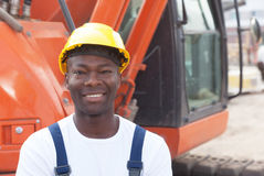Happy african construction worker with red excavator Royalty Free Stock Photography