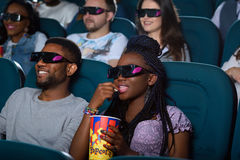 Happy African couple at the cinema. Lost in the world of action. Portrait of a beautiful African women sipping her drink while enjoying a movie together with her Stock Image