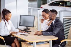 Happy african couple with dealer buying car in auto show or salon. Auto business, sale and people concept - happy african couple with dealer buying car in auto royalty free stock photo
