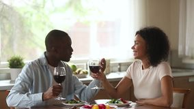 Happy african couple enjoy talking drinking wine sit at table. Happy young african couple in love enjoy talking eating drinking wine sit at table on romantic stock video footage