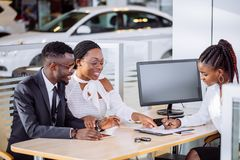 Happy african couple with dealer buying car in auto show or salon. Happy African couple and female seller sit at table and make a deal for sale of car royalty free stock images