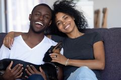 Happy african couple playing with dog sitting on couch, portrait. Happy african american couple playing with dog sit on couch looking at camera, excited black stock images