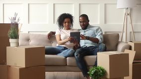 Happy african couple use digital tablet on moving day