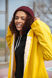 Happy african curly young lady wearing yellow coat walking outdoors Royalty Free Stock Images