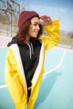 Happy african curly young woman wearing yellow coat walking Royalty Free Stock Photography