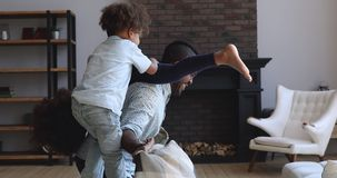 Happy african dad having fun with active kids at home