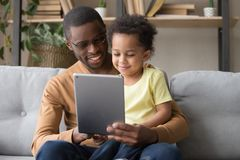 Happy african dad and little son using tablet at home royalty free stock photo