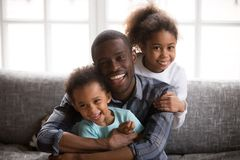 Happy african dad and mixed race children at home portrait. Happy african american dad and mixed race children, cheerful black family daddy embracing little son stock image