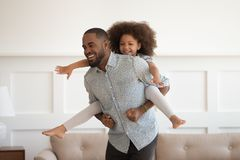 Happy african dad piggybacking little daughter having fun at home. Happy african american dad piggybacking little funny daughter having fun at home, laughing royalty free stock photos