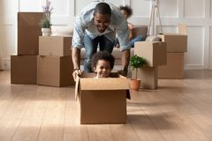 Happy african dad playing with little son riding in box. Happy african dad playing with cute little mixed race son looking at camera laughing on moving day stock photography