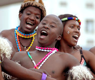 Happy African dancers singing. A group of South African Zulu dancers and singers entertaining and performing for the spectators and tourists at the Ironman royalty free stock images