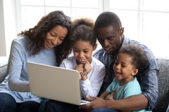 Happy african family with children using laptop together at home royalty free stock photography