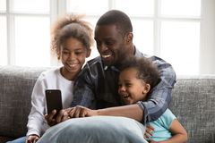 Happy African father with kids using smartphone. Happy African family spending time have a fun together using mobile phone at home. Black father with little royalty free stock photos