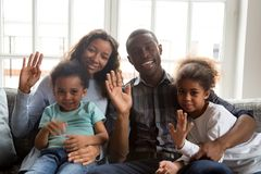 Free Happy African Family With Kids Waving Hands Looking At Camera Stock Images - 136499524