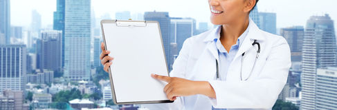 Happy african female doctor with clipboard Royalty Free Stock Images
