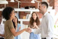 Happy african female worker getting promoted handshaking caucasian boss stock photo