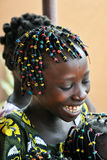 Happy African girl. Burkina Faso, Africa. A happy African girl with a beautiful smile and colorful hairstyle Royalty Free Stock Images