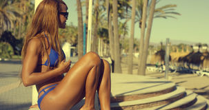 Happy African Girl in Bikini Sits at Beach Bench Stock Images