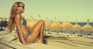 Happy African Girl in Bikini Sits at Beach Bench Royalty Free Stock Image