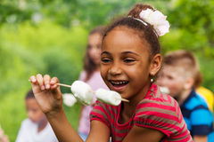 Happy African girl holding stick with marshmallow royalty free stock image